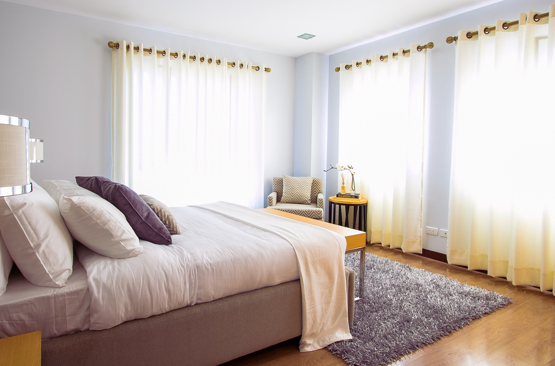 An image of a bedroom, complete with scatter cushions, and curtains hung on a wooden curtain pole.