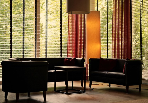 An image of a living room with floor to ceiling horizontal blinds.