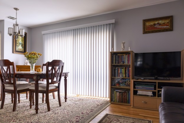An image vertical blinds from Elite Blinds (UK), hanging in a dining room.