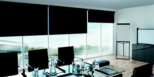 An image of a black roller blind hung at an office window.