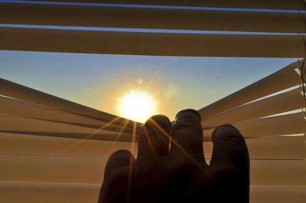 image of a hand pulling down blinds to let in sun